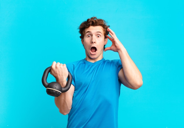 Young sport boy screaming with hands up in the air, feeling furious, frustrated, stressed and upset. dumbbell concept