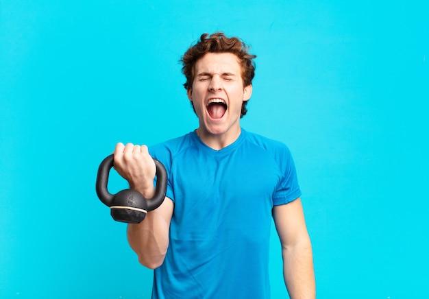 Молодой спортивный мальчик агрессивно кричит, выглядит очень злым, расстроенным, возмущенным или раздраженным, кричит «нет». гантели