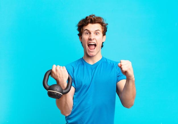 Молодой спортивный мальчик агрессивно кричит с сердитым выражением лица или со сжатыми кулаками, празднуя успех. гантели