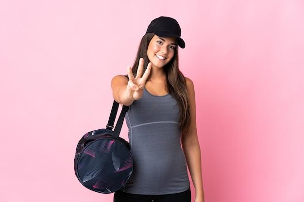 幸せなピンクの壁に分離されたスポーツバッグと指で3を数える若いスポーツブラジルの女の子