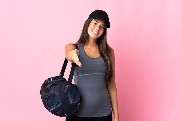 Молодая спортивная бразильская девушка со спортивной сумкой, изолированной на розовой стене, пожимая руку для заключения хорошей сделки