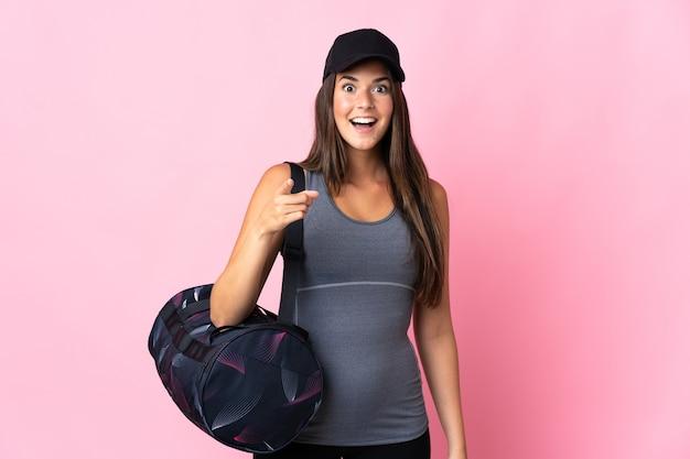 젊은 스포츠 브라질 여자 스포츠 가방 놀라게 하 고 앞을 가리키는 분홍색 벽에 고립