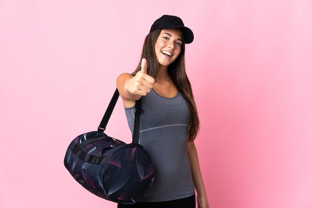 좋은 일이 일어났기 때문에 엄지 손가락으로 분홍색 벽에 고립 된 스포츠 가방을 가진 젊은 스포츠 브라질 소녀