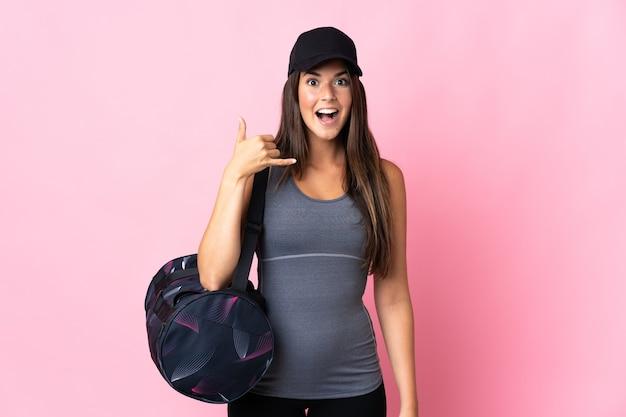 電話ジェスチャーを作るピンクのスポーツバッグを持つ若いスポーツブラジルの女の子