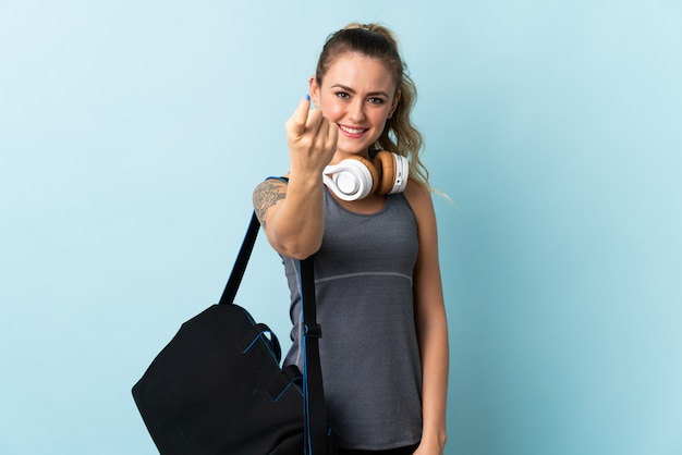 Young sport brazilian woman with sport bag isolated on blue doing coming gesture