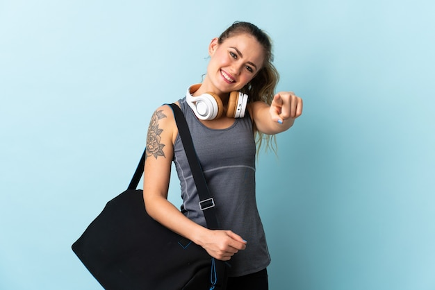 Young sport brazilian woman with sport bag isolated on blue pointing front with happy expression