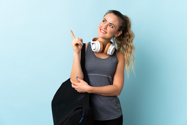 Young sport brazilian woman with sport bag isolated on blue pointing up a great idea