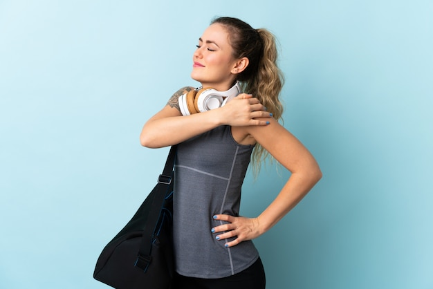 Young sport brazilian woman with sport bag isolated on blue suffering from pain in shoulder for having made an effort