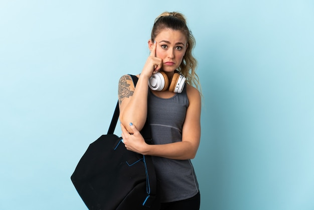 Young sport brazilian woman with sport bag isolated on blue thinking an idea