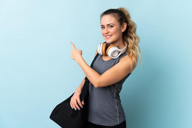 Молодая спортивная бразильская женщина со спортивной сумкой, изолированной на синем фоне, указывая назад