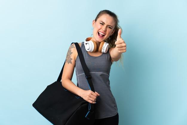 좋은 일이 일어났기 때문에 엄지 손가락으로 파란색 배경에 고립 된 스포츠 가방 젊은 스포츠 브라질 여자