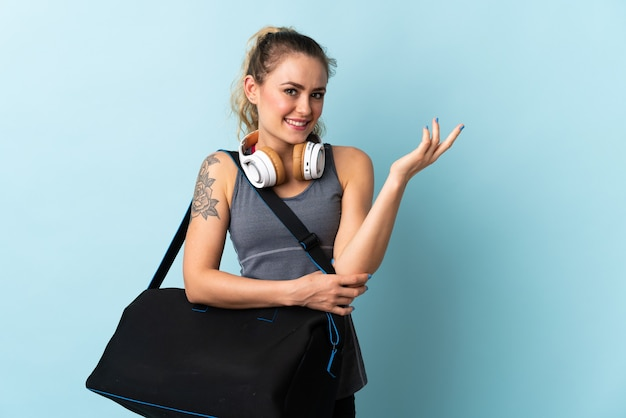 젊은 스포츠 브라질 여자 스포츠 가방은 올 초대를 위해 옆으로 손을 확장 파란색에 고립