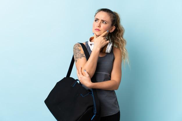 Молодая спортивная бразильская женщина со спортивной сумкой, изолированная на синем, имеющая сомнения