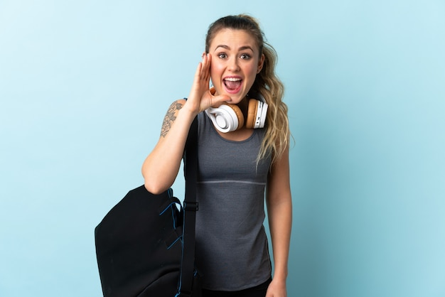Молодая спортивная бразильская женщина со спортивной сумкой изолирована на синем и кричит с широко открытым ртом