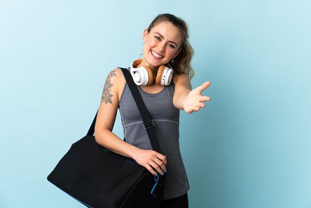 Молодая спортивная бразильская женщина со спортивной сумкой, изолированной на синей стене, пожимая руку для заключения хорошей сделки