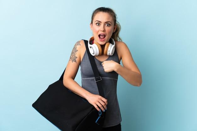Молодая спортивная бразильская женщина со спортивной сумкой изолирована на синем с удивленным выражением лица