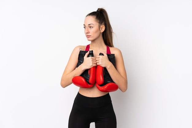 Young sport brunette woman over isolated white wall with boxing gloves