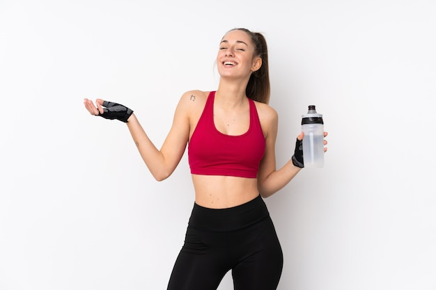 Young sport brunette woman over isolated white wall with sports water bottle