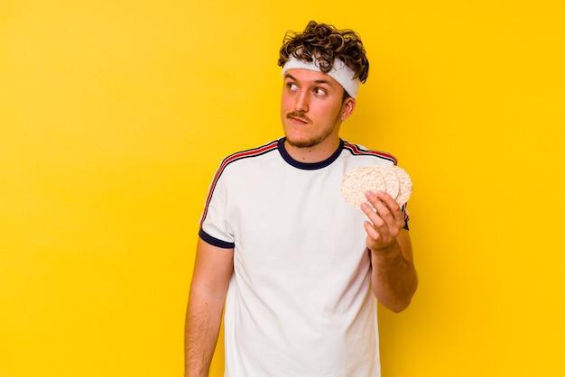 목표와 목적을 달성하는 꿈을 꾸고 노란색 벽에 고립 된 떡을 먹는 젊은 스포츠 백인 남자