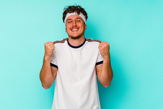 Young sport caucasian man isolated on blue background cheering carefree and excited. victory concept.