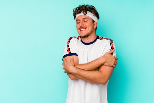 Young sport caucasian man isolated on blue wall hugs, smiling carefree and happy.