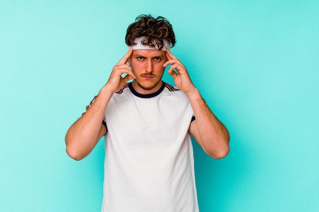 Молодой спортивный кавказец, изолированные на синем фоне, сосредоточился на задаче, держа указательные пальцы, указывая головой.