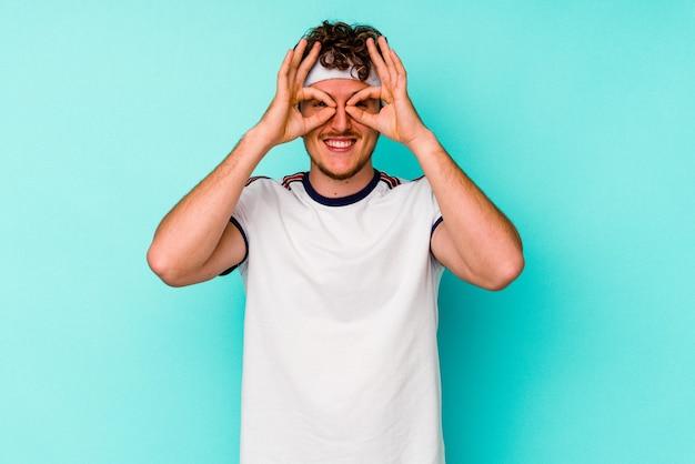 Молодой спортивный кавказский человек, изолированные на синем фоне, показывает хорошо, знак над глазами