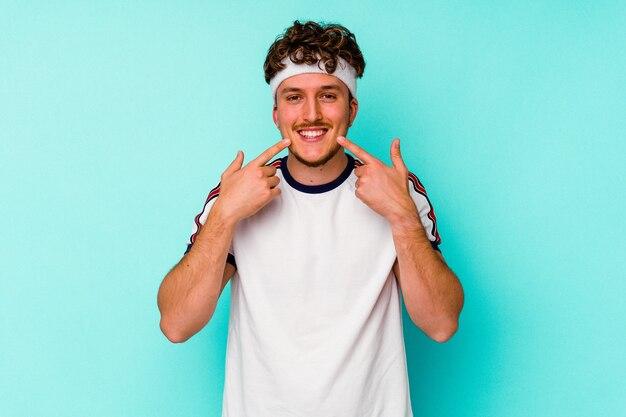 青い背景に孤立した若いスポーツ白人男性は、口に指を指して微笑んでいます。