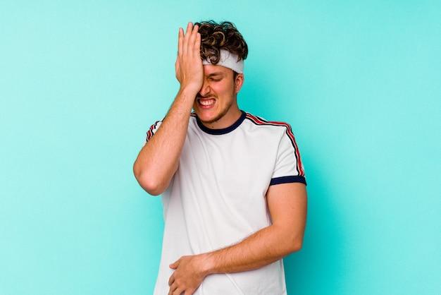 何かを忘れて、手のひらで額を平手打ちし、目を閉じて青い壁に孤立した若いスポーツ白人男性。