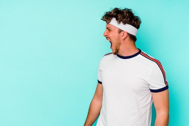 복사 공간을 향해 외치는 파란색 벽에 고립 된 젊은 스포츠 백인 남자