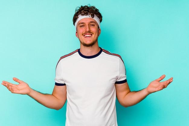 Молодой спортивный кавказец, изолированные на синей стене
