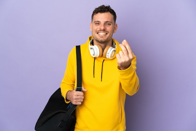 Young sport caucasian man with bag isolated making money gesture