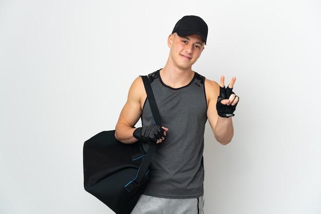 Молодой спортивный кавказец с сумкой, изолированной на белом фоне, улыбается и показывает знак победы
