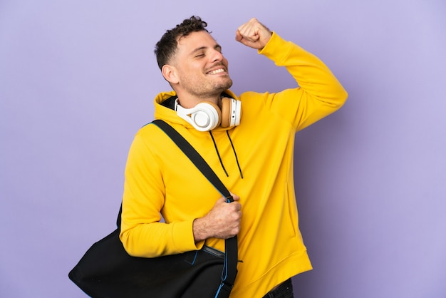 Young sport caucasian man with bag isolated purple wall celebrating a victory