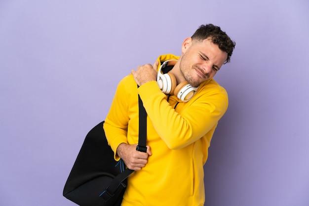 努力をしたために肩の痛みに苦しんでいるバッグ孤立した紫色の壁を持つ若いスポーツ白人男性