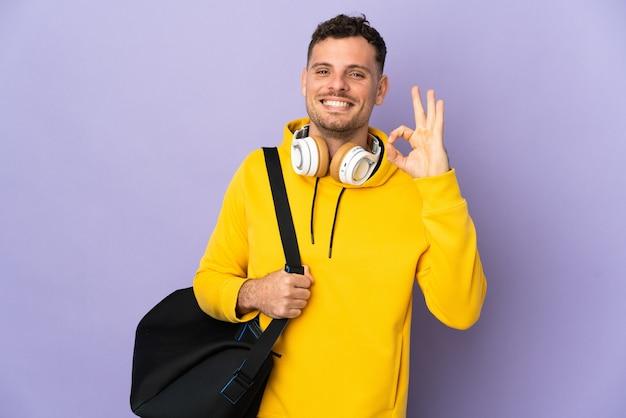 Молодой спортивный кавказец с изолированной сумкой показывает знак ок с пальцами