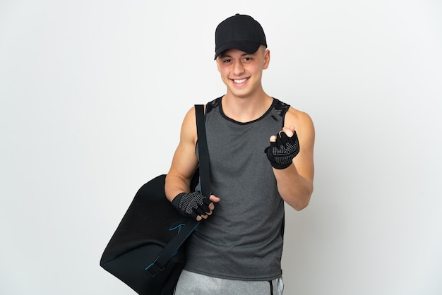 Young sport caucasian man with bag isolated on white making money gesture