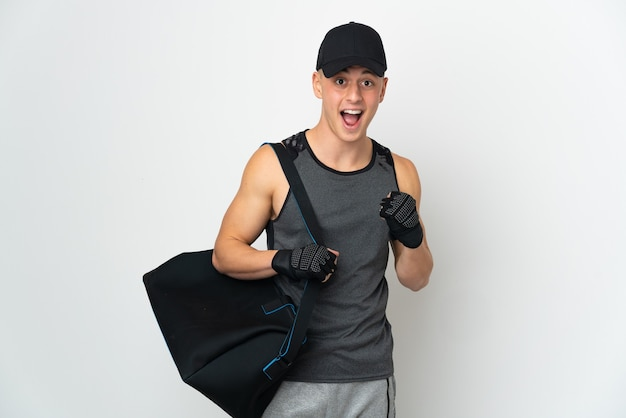 Young sport caucasian man with bag isolated on white wall celebrating a victory in winner position