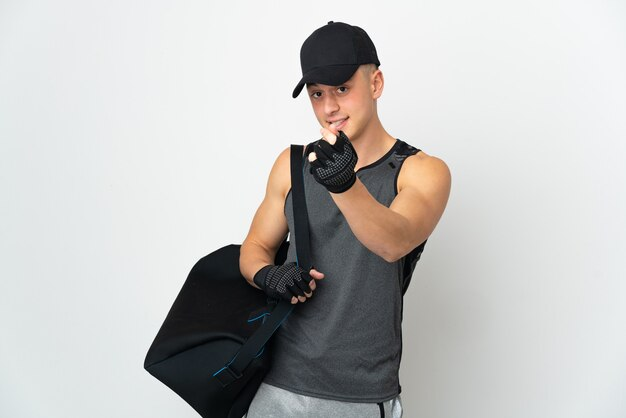 Young sport caucasian man with bag isolated on white wall making money gesture
