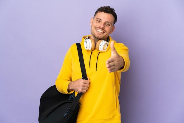 Молодой спортивный кавказец с изолированной сумкой