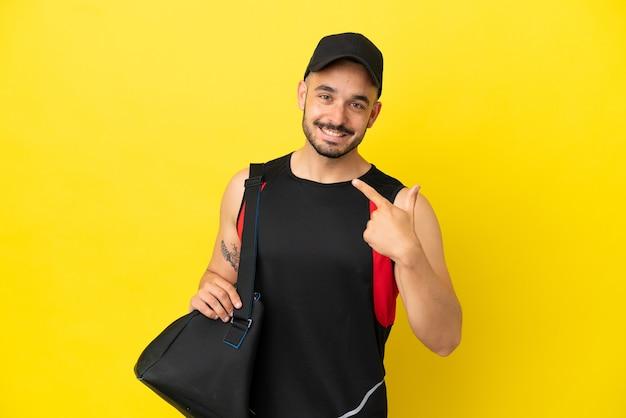 Молодой спортивный кавказец со спортивной сумкой, изолированной на желтом фоне, показывает палец вверх жестом