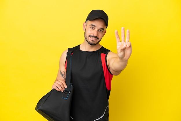 Молодой спортивный кавказец со спортивной сумкой, изолированной на желтом фоне, счастлив и считает три пальцами