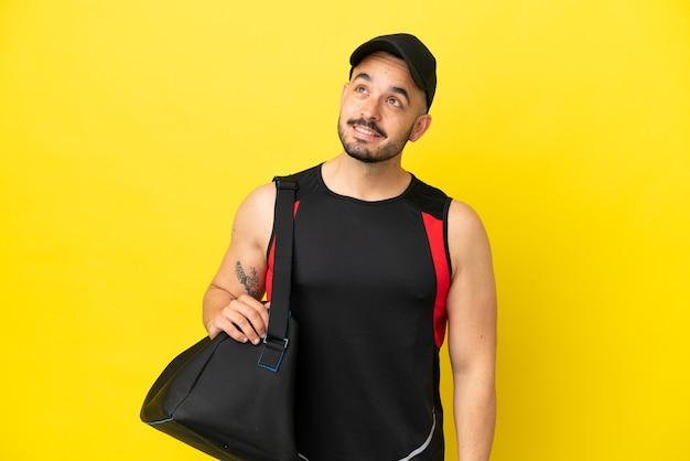 見上げながらアイデアを考えて黄色の背景に分離されたスポーツバッグを持つ若いスポーツ白人男性