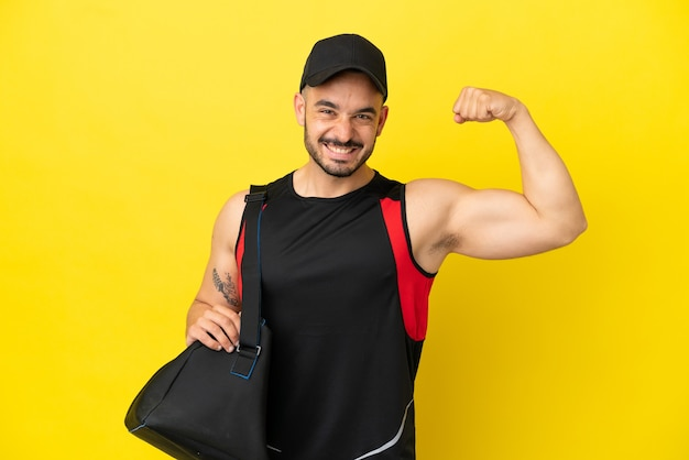 Young sport caucasian man with sport bag isolated on yellow background doing strong gesture