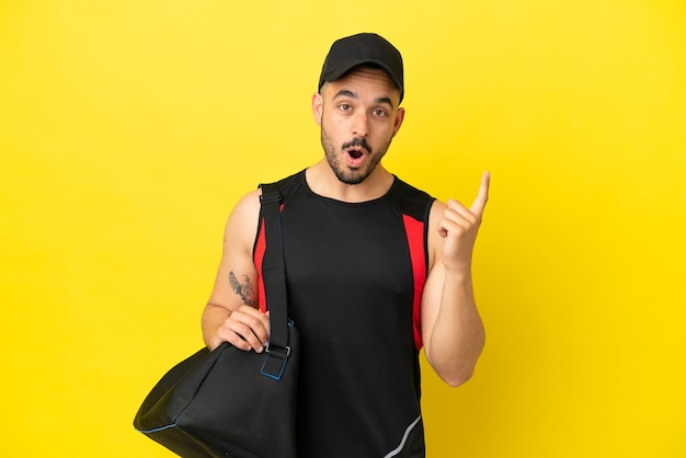 Young sport caucasian man with sport bag isolated on yellow background intending to realizes the solution while lifting a finger up