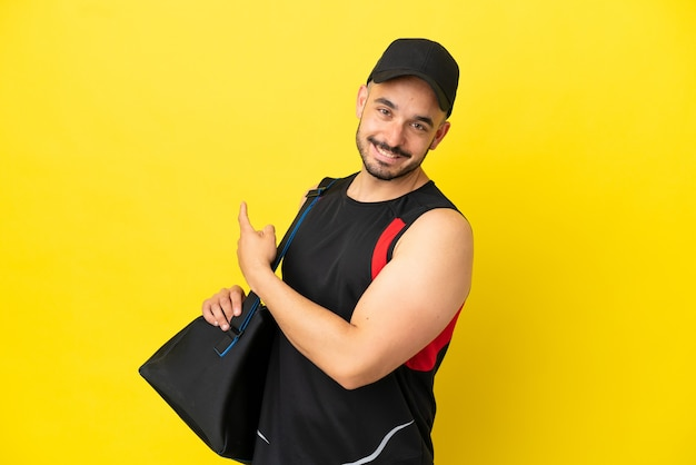 Young sport caucasian man with sport bag isolated on yellow background pointing back