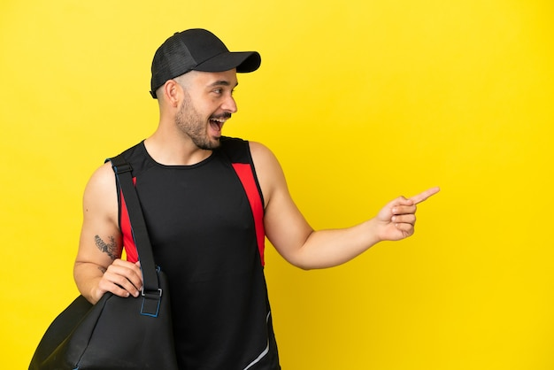 Young sport caucasian man with sport bag isolated on yellow background pointing finger to the side and presenting a product