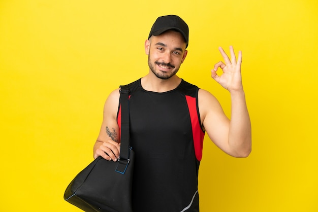 Young sport caucasian man with sport bag isolated on yellow background showing ok sign with fingers