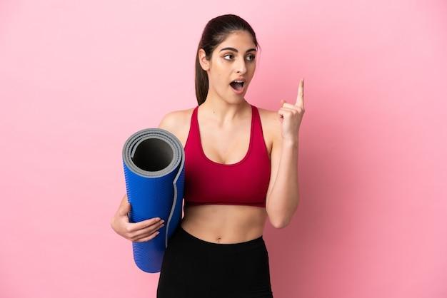 Молодая спортивная кавказская женщина идет на занятия йогой, держа коврик, думая об идее, указывая пальцем вверх