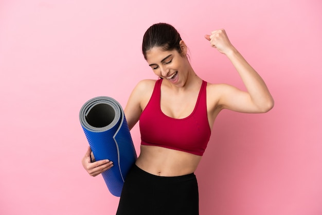 Young sport caucasian woman going to yoga classes while holding a mat celebrating a victory
